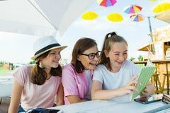 Los adolescentes de la mamá y de las hijas se divierten, miran y leen el libro divertido Comunicación del padre y de los niños de imagenes de archivo