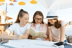 Los adolescentes de la mamá y de las hijas tienen la diversión, hablar, mirada y libro divertido leído Comunicación del padre y d fotografía de archivo libre de regalías