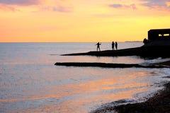 Los adolescentes de la playa de Brighton de la puesta del sol que juegan en las aguas afilan Fotos de archivo libres de regalías