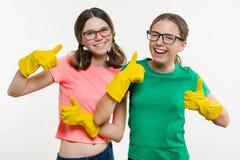 Los adolescentes de las muchachas que llevan guantes protectores amarillos muestran los pulgares para arriba Imagen de archivo libre de regalías