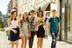 Los adolescentes de los niños van con su profesor Los estudiantes felicitaron a la hembra con el ramo de flores Día del ` s del p Imagen de archivo libre de regalías