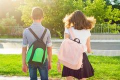 Los adolescentes de los niños van a la escuela, visión trasera Al aire libre, adolescencias con las mochilas Imagen de archivo