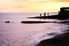 Los adolescentes de Silhoutted que juegan en las aguas afilan en la puesta del sol Imagenes de archivo