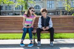 Los adolescentes del muchacho y de la muchacha juegan, leído, mirada en el smartphone En el banco, el fondo urbano Fotografía de archivo libre de regalías