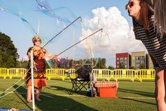 Los adolescentes dirigen la burbuja masiva soplando en él Fotografía de archivo libre de regalías
