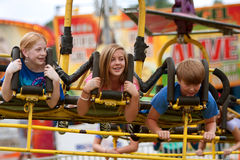 Los adolescentes disfrutan de un paseo emocionante del carnaval Imagenes de archivo