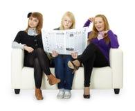 Los adolescentes divertidos de la muchacha leyeron el periódico Fotos de archivo libres de regalías