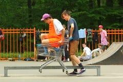 Los adolescentes divertidos realizan trucos en la barandilla en una carretilla en skatepark del público de la ciudad Imagen de archivo libre de regalías