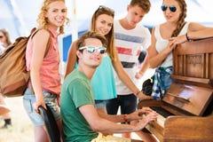 Los adolescentes en el festival de música del verano, muchacho juegan el piano Foto de archivo libre de regalías