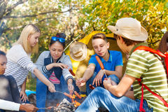 Los adolescentes en las salchichas de la parrilla del sitio para acampar acercan a la hoguera Fotos de archivo libres de regalías