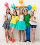 Los adolescentes en una fiesta de cumpleaños están abrazando Imagen de archivo libre de regalías