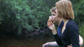 Los adolescentes enamorados se sientan en el fondo de la naturaleza y hablan con uno a metrajes