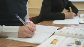 Los adolescentes escriben el texto en cuaderno en una lección almacen de video