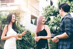 Los adolescentes están disfrutando de una fiesta de jardín en casa y están sosteniendo el vidrio de cerveza a disposición foto de archivo