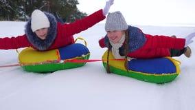 Los adolescentes felices de los niños ruedan en la placa nevosa a lo largo del camino nevoso blanco y de la risa Las muchachas al almacen de video