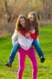 Los adolescentes felices llevan a cuestas el montar a caballo en prado Fotos de archivo libres de regalías