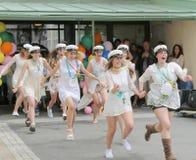 Los adolescentes felices que llevan la graduación capsulan el funcionamiento hacia fuera de la escuela Imagen de archivo libre de regalías
