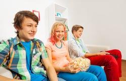 Los adolescentes felices sostienen las palomitas y se sientan en el sofá Fotos de archivo