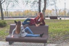 Los adolescentes femeninos en el banco en una ciudad del otoño parquean Imagen de archivo