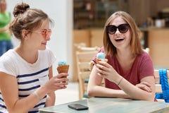Los adolescentes femeninos felices tienen miradas positivas, comen el helado frío de la fruta en café, estando en humor de dios,  Imágenes de archivo libres de regalías