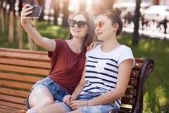 Los adolescentes femeninos positivos se sientan en de madera en banco en parque verde, presentan para hacer el selfie, miran el t Fotografía de archivo