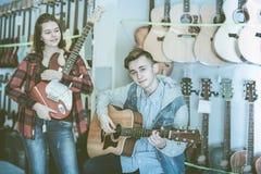 Los adolescentes jovenes del roca-n-rollo están eligiendo entre acústico y el EL Imágenes de archivo libres de regalías