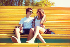 Los adolescentes jovenes felices de los pares se están sentando en la ciudad del banco Fotografía de archivo