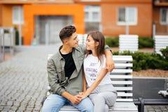 Los adolescentes jovenes felices de los pares se están sentando en la ciudad del banco en el día soleado del verano Imagen de archivo