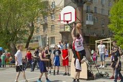 Los adolescentes juegan el streetball en la tierra al aire libre del asfalto Imágenes de archivo libres de regalías