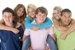 Los adolescentes llevan a cuestas en muchachos Fotos de archivo