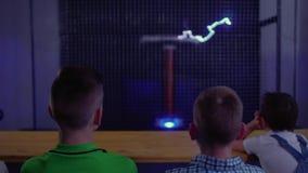 Los adolescentes miran la demostración musical con el relámpago del baile de la bobina de tesla almacen de metraje de vídeo