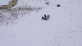 Los adolescentes montan encendido con las montañas nevosas blancas y risa Días de fiesta de la Navidad Modelado dinámico del cará almacen de metraje de vídeo