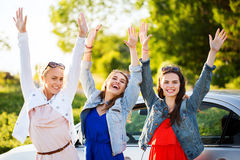 Los adolescentes o las mujeres felices acercan al coche en la playa Foto de archivo