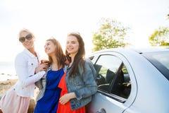 Los adolescentes o las mujeres felices acercan al coche en la playa Imágenes de archivo libres de regalías