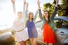 Los adolescentes o las mujeres felices acercan al coche en la playa Imagen de archivo libre de regalías
