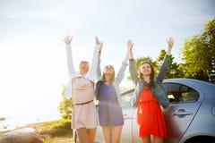 Los adolescentes o las mujeres felices acercan al coche en la playa Imagenes de archivo
