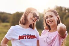 Los adolescentes positivos alegres se divierten junto, encantando sonríen en las caras, aire del verano de la respiración y admir Imagen de archivo libre de regalías