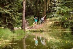 Los adolescentes practican yoga en el lago en bosque Foto de archivo