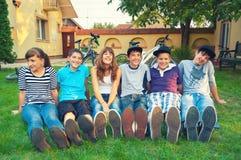 Los adolescentes que descansan sobre la hierba después de bicicleta montan Fotos de archivo libres de regalías