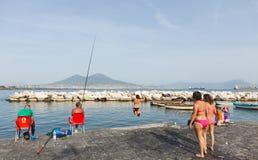 Los adolescentes que saltan en el mar en Nápoles Foto de archivo libre de regalías