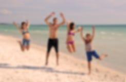 Los adolescentes que saltan en la playa Imagen de archivo libre de regalías