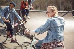 Los adolescentes que se divierten y que montan las bicicletas en monopatín parquean Foto de archivo