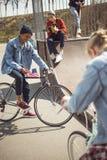 Los adolescentes que se divierten y que montan las bicicletas en monopatín parquean Imagenes de archivo