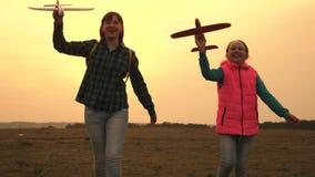 Los adolescentes quieren hacer piloto y astronauta Las muchachas felices corren con el avi?n del juguete en la puesta del sol en  almacen de metraje de vídeo