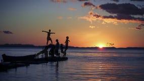 Los adolescentes se divierten en la playa en la puesta del sol Imagenes de archivo