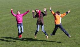 Los adolescentes y el muchacho gozan al salto Imagen de archivo libre de regalías