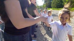 Los adolescentes y los equipos de los niños que se saludan con sacuden las manos en el día soleado del verano metrajes