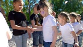 Los adolescentes y los equipos de los niños que se saludan con sacuden las manos en el día soleado del verano almacen de metraje de vídeo
