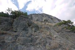 Los adoquines de piedra grandes dispersaron a lo largo de una montaña rocosa con la hierba seca y los arbustos verdes Fotografía de archivo