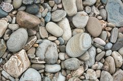 Los adoquines grises redondearon por la erosión del río en una cama de río anterior Imágenes de archivo libres de regalías